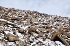 Fresh snow on stones of mountains stock photo