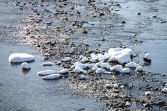 Snow on the stones in the river. And the snow-reflected sunlight Royalty Free Stock Images