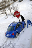Snow-stopped. Man and woman digging out a car stuck in the snow at a stop sign Royalty Free Stock Images
