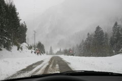 Snow storm in the mountain inside a car. Snow storm in a foggy mountain viewed from inside of a car driving along a snowy road Stock Photo