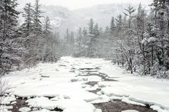 Snow storm on swift river Stock Photos