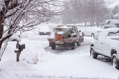 Snow Storm Working Snowplow Housing Development. Snowplow clearing the roads during a snow storm in a Virginia suburban housing development in winter Royalty Free Stock Photo