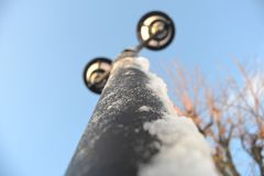 Snow on streetlamp. Snow on a streetlamp on a beautiful day taken from a frog perspective Royalty Free Stock Photography