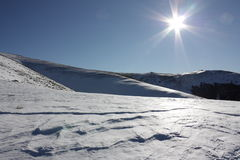 Snow and sun in Pyrenees. Snowy mountain(Dourmidou peak) and sun in Pyrenees,Aude,Languedoc region of France Royalty Free Stock Image