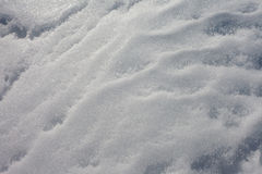Snow surface full frame background texture pattern. Wind and thaw-freeze cycles created patterns on surface of packed snow Stock Photo
