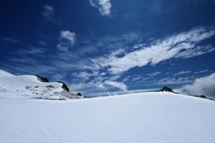 Snow surface of mountains with blue sky and clouds Stock Photography