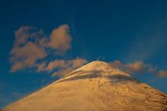 Snow-täckt berg som är maximalt med moln på solnedgången royaltyfri bild
