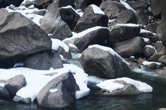 Snow-täckt vaggar i liten vik Arkivfoto