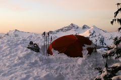 Snow Tent. Taken on Mt. Rainier during a boy scout expedition, the morning sun backlit a tent partially covered by snow the preceeding night stock photography