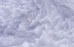 Snow texture. Snow wall with deep horizontal crevasses caused by melting and re-freezing royalty free stock photography