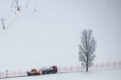 Snow thrower and dump truck. Municipal snow removal crew at work; snow thrower and dump truck on street with skiing slope in the background Stock Images