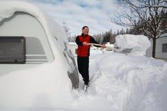 Snow throwing. Man throwing snow around the caravan Stock Photo