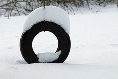 Snow Tire Swing. A snow covered tire swing alone on a cold winter day in a rural country yard Stock Photography