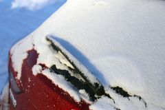 Snow on Top of the Rear Window of a Red Car. Photographed under daylight during winter in Finland royalty free stock photos