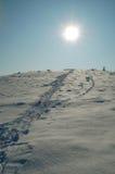Snow trail to sun stock photos