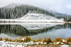 Snow, trees, and foothills reflected in Sibbald Pond. Kananaskis Country, Alberta, Canada Royalty Free Stock Images