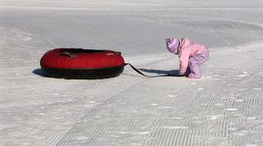 Snow Tubing. Winter scene of a toddler and her snow tube Stock Image
