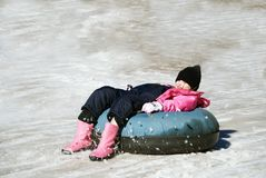 Snow tubing fun. Girl sliding down the slope dragging her feet and making the snow fly stock photos