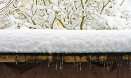Snow on twigs and wooden roof Stock Photos