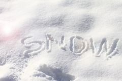 """snow Utdragen """"snow"""" för hand i den nya snön Att skriva för hand suckar insnöat snön Textur för vinterbegreppsbakgrund kopier royaltyfria foton"""