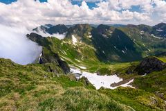 Snow in the valley of Fagaras mountains. Beautiful summer scenery on a cloudy day. dappled light on grassy slopes Stock Photos