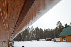 Snow visor with icicles  slipping from canopy roof. Spring sleet in the village. Siberia, Russia Stock Photos