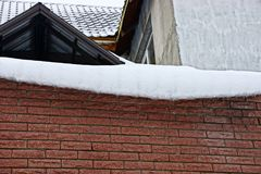 Snow white drift on a brown brick wall. Snow white drift on the brown brick wall of the house Royalty Free Stock Images