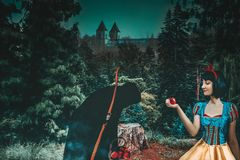Snow White girl with old evil witch gives her an apple in the mysterious forest closeup. Artistic processing.  royalty free stock image
