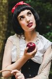Snow White holds a red apple in her hand and looks up with a candid face stock images