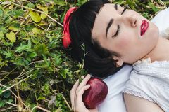 Snow White is laying in the floor. She seems to be in a profound sleep stock photos
