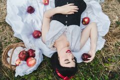 Snow White is laying in the floor, surrounded by red apples. She seems to be in a profound sleep. royalty free stock photo