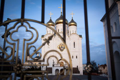 Snow White Orthodox church. Snow White orthodox temple with gold domes standing on the other side of the fence wrought royalty free stock photo