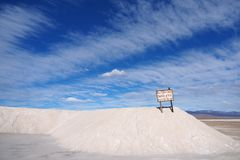 A pile of salt, blue sky and scenic clouds stock image
