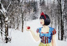 Snow White with red apple in the mysterious snowy forest. Artistic processing.  stock photo