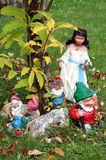 Snow White and Seven Dwarfs. Closeup of Snow White and the Seven Dwarfs garden gnomes under leafy tree Stock Images