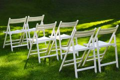 Snow-white wooden chairs for guests at an outdoor wedding ceremony. Snow-white wooden chairs for guests at an wedding ceremony outdoor  on green background stock photography