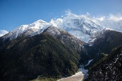 Snow and windy peaks of Annapurna II, Annapurna IV and Annapurna III mountains as seen from Upper Pisang village royalty free stock image