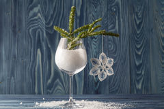 Snow in wine glass, tree branches and Christmas balls on old woo. Den background, selective focus Royalty Free Stock Image