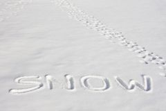 SNOW Written In A Snowy Field Beside Footprints Stock Photos