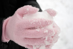 Snowball. Hands in gloves pink snow mold.Winter fun game Royalty Free Stock Photography