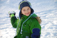 Snowball boy. A boy winds up to throw a snowball Royalty Free Stock Photos