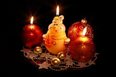 Cute snowman and Christmas candles and toys. Burning candle and New Year's toys on a black background Stock Image