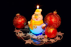 Cute snowman and Christmas  toys. Burning candle and New Year's toys on a black background Stock Images
