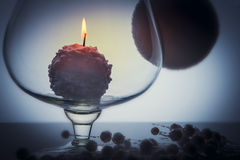 Snowball candle burning inside glass goblet Stock Image