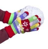 Snowball de blanc filète dans des mains du ` s d'enfant, plaquées dans les gants colorés d'isolement sur le fond blanc, nouvelle  Photographie stock