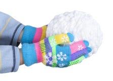 Snowball de blanc filète dans des mains du ` s d'enfant, plaquées dans les gants colorés d'isolement sur le fond blanc, nouvelle  Images stock