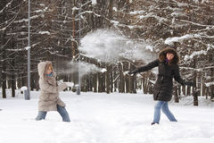 Snowball fight. Two friend women at snowball fight in winter forest Royalty Free Stock Photo