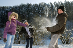 Snowball fight. Three young people have a snowball fight royalty free stock photography