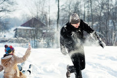 Snowball fight!. Winter collection: young couple playing with snow Royalty Free Stock Image