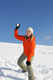 Snowball fight. Young pretty girl playing snowball fight on flank of hill stock images